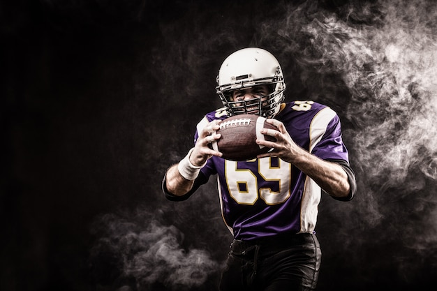 Palla della tenuta del giocatore di football americano in sue mani in fumo