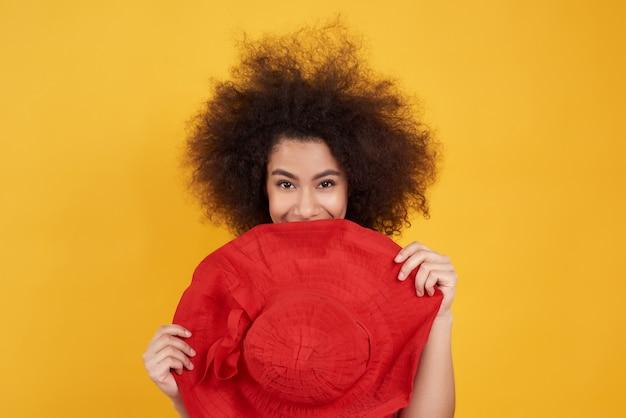 Ragazza americana con la posa del cappello rosso su giallo.