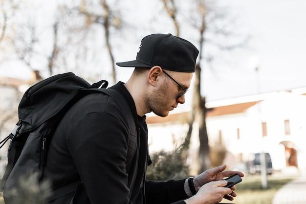 Il giovane americano di bell'aspetto in occhiali da sole in vestiti neri in berretto da baseball di moda con zaino con telefono cellulare si siede sulla strada. il modello di moda del bel ragazzo urbano sta guardando nello smartphone