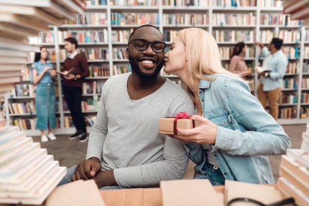 Ragazzo americano e ragazza bianca circondata da libri.