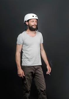 Uomo barbuto bello americano in un casco da bicicletta. dispositivo di sicurezza per proteggere la salute. sigaretta di fumo dell'uomo russo serio. sport e abitudine dannosa. il fumo provoca il cancro ai polmoni e altre malattie.