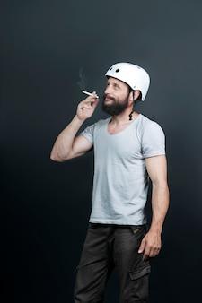 Uomo barbuto bello americano in un casco da bicicletta. smettere di fumare. uomo russo che fuma sigaretta dopo un intenso allenamento in bicicletta. sport e abitudine dannosa. persona attiva che si gode i momenti della vita quotidiana
