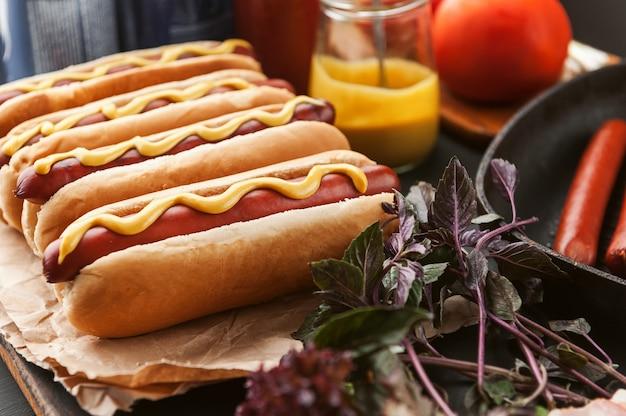 Hot dog americano con ingredienti su uno sfondo di legno scuro