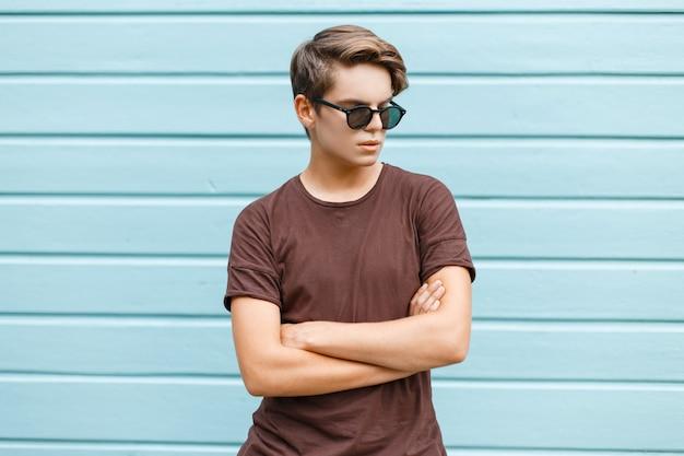 Il giovane americano hipster moderno in occhiali da sole alla moda in maglietta marrone alla moda si trova vicino a una casa blu in legno vintage in città in un giorno d'estate