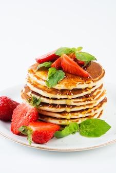 Pancakes americani foderati con fragole e miele versato su uno sfondo bianco. colazione americana classica.