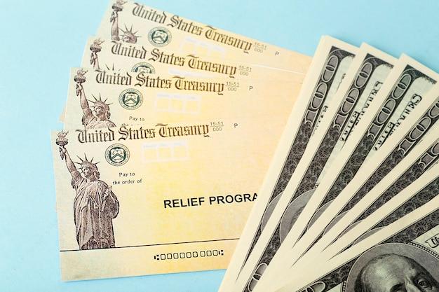 Assegni del programma di soccorso americano e banconote in dollari su sfondo blu