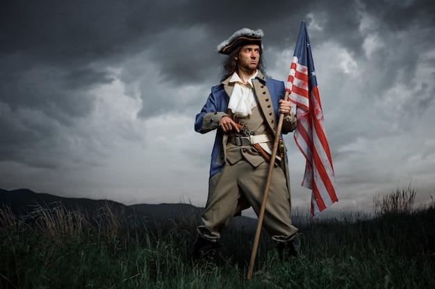 Soldato di guerra di rivoluzione americana con la bandiera delle colonie sul paesaggio drammatico