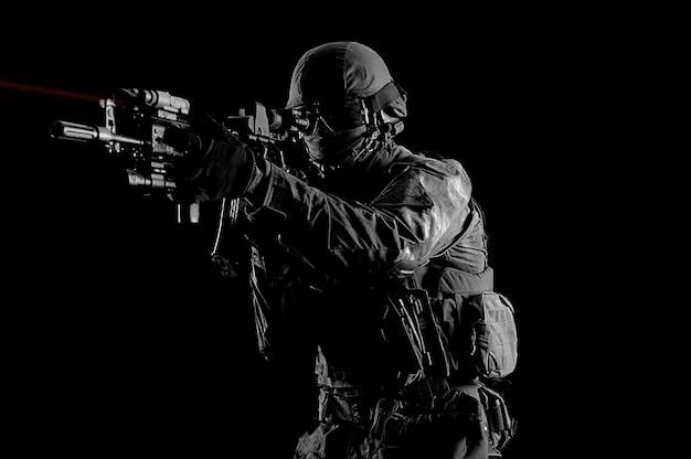 Soldato americano in munizioni da combattimento con un'arma dotata di mirini laser mira al bersaglio. tecnica mista