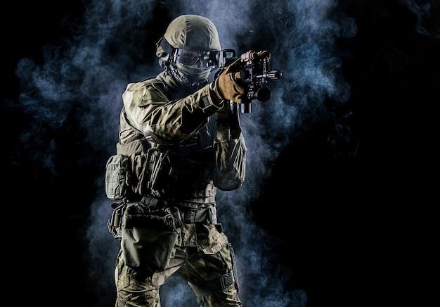 Soldato americano in munizioni da combattimento con arma nelle mani di mirini laser equipaggiati è in ordine di battaglia. tecnica mista
