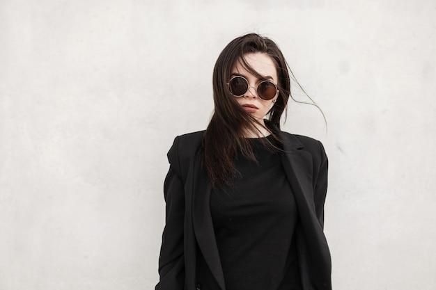 La giovane donna americana alla moda con capelli castani con labbra sexy in occhiali da sole rotondi alla moda in blazer vintage nero in t-shirt alla moda si trova vicino al muro bianco in città. ragazza moderna fresca in abito nero.