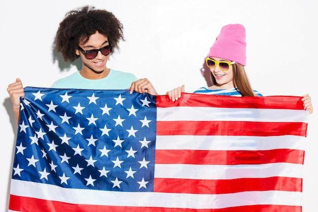 Adolescenti americani. funky giovane coppia che tiene la bandiera americana di fronte a loro e sorride mentre sta in piedi su sfondo bianco white