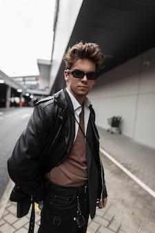 Americano hipster alla moda giovane in occhiali da sole in una giacca di pelle nera alla moda oversize giovanile con un'acconciatura alla moda si trova vicino a un edificio d'epoca in una città. ragazzo moderno urbano in strada.