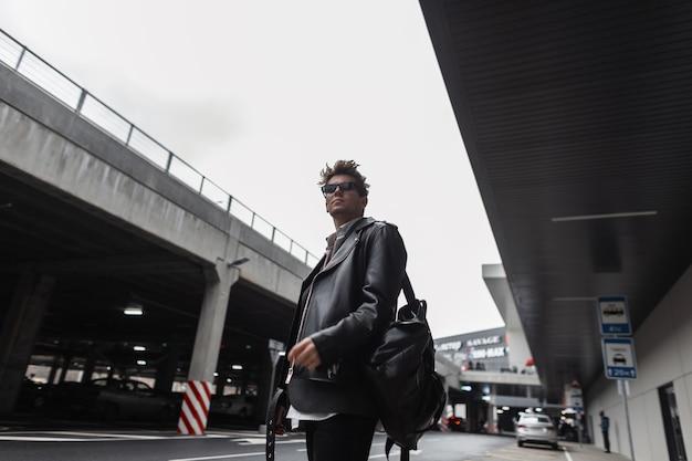 Modello di giovane uomo alla moda americano in una giacca di pelle nera alla moda oversize giovanile con acconciatura con zaino si trova vicino a un edificio moderno della città. bel ragazzo hipster in occhiali da sole all'aperto.