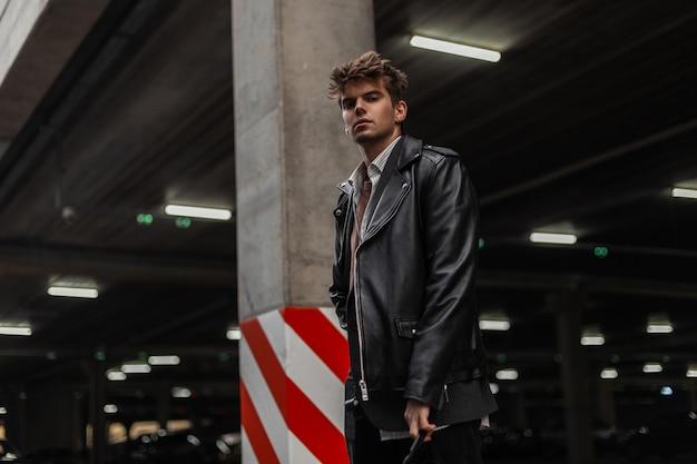 Modello di giovane uomo alla moda americano in una giacca di pelle nera alla moda oversize giovanile con un'acconciatura alla moda si trova vicino a una colonna vintage in un parcheggio cittadino. ragazzo moderno hipster urbano in strada