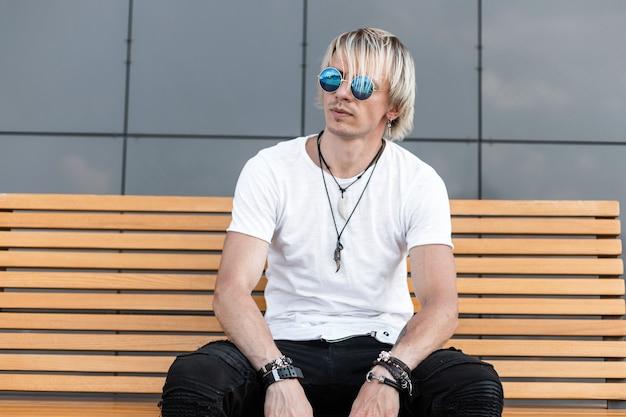 Il giovane urbano americano in jeans neri in maglietta bianca in occhiali da sole alla moda è seduto su una panca di legno vicino a un edificio grigio. il ragazzo elegante e alla moda gode di riposo in città. moda moderna estiva