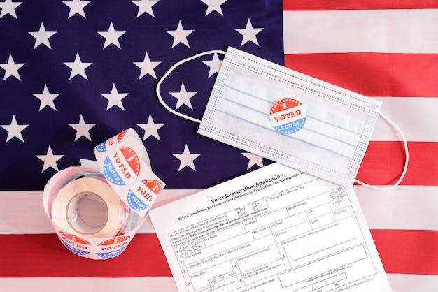 Gli elettori americani devono registrarsi compilando un modulo anche durante la pandemia, indossando una maschera facciale durante il voto.