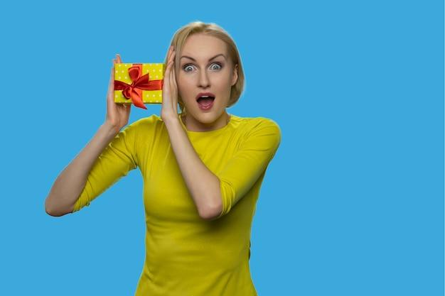 La donna americana con la bocca aperta tiene in mano una confezione regalo