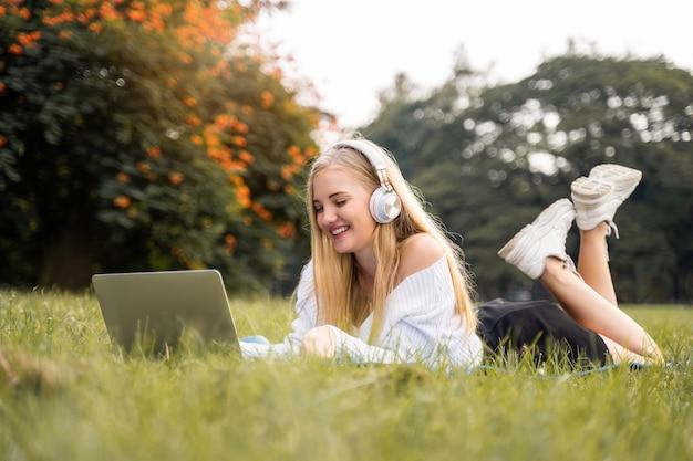 Donne americane che si siedono con le felicità sorridenti e ascoltano la musica nel parco per rilassarsi