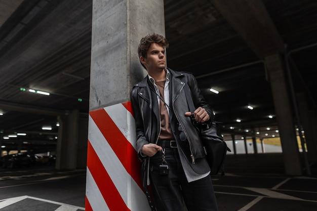 Giovane americano in una giacca di pelle nera alla moda in una camicia classica con uno zaino vintage con un'acconciatura in posa vicino a un pilastro con una linea rosso-bianca in un parcheggio cittadino. ragazzo trendy urbano cool