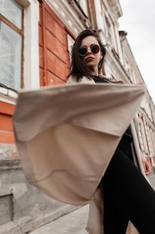 Hipster americano giovane donna in occhiali da sole moda in jeans casual eleganti neri in trench moda primavera filatura all'aperto vicino al vecchio edificio sulla strada. modello urbano della ragazza in vestiti della gioventù in città.