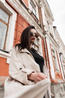 Hipster americano giovane donna in occhiali da sole moda in camicia casual elegante nera in trench moda primavera filatura all'aperto vicino al vecchio edificio sulla strada. modello urbano della ragazza in vestiti della gioventù in città.
