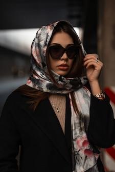 Il modello americano della giovane donna in un cappotto nero in occhiali da sole alla moda con le labbra sexy mette sopra una sciarpa di seta elegante alla moda sopra la testa. ragazza attraente moderna di affari del ritratto alla moda in strada.