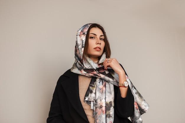 Modello americano della giovane donna in un cappotto nero con pelle fresca con le labbra sexy con la sciarpa di seta elegante alla moda sulla testa vicino alla parete dell'annata. ragazza attraente moderna di affari del ritratto alla moda in strada.