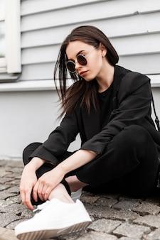 La giovane donna americana in occhiali da sole alla moda in bei vestiti neri della gioventù in scarpe da ginnastica alla moda bianche riposa su mattonelle di pietra vicino all'edificio d'epoca in città. ragazza cool in abbigliamento casual alla moda. stile di strada.