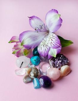 Fiori di ametista, strass, agata, quarzo rosa, acquamarina e alstroemeria su una superficie rosa