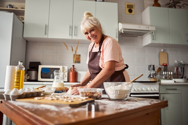 Donna anziana amichevole che prepara pasto al tavolo della cucina