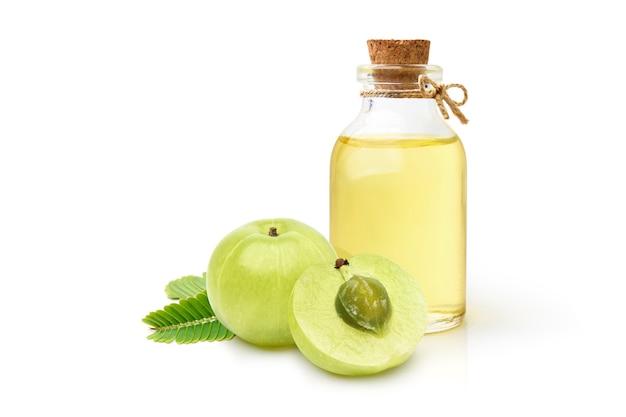 Olio di amla (uva spina indiana) con frutta e foglia isolato su sfondo bianco.