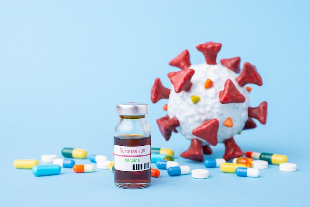 Ampolla di vaccino covid-19, pillole colorate e modello di coronavirus su un tavolo blu