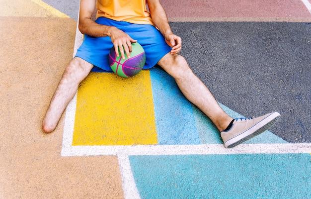 Ragazzo amputato che gioca a basket al parco e fa sport. concetto di disabilità e persistenza