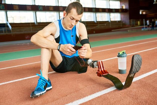 Amputato sportivo seduto sul pavimento