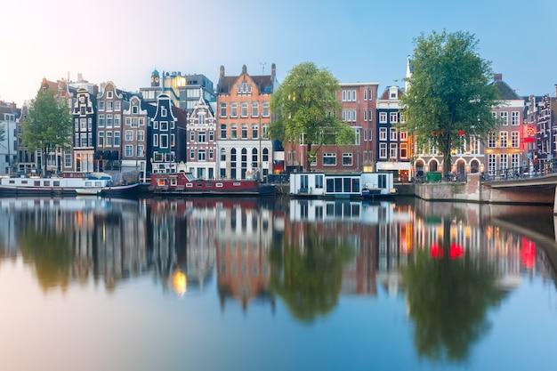 Amsterdam canal amstel con tipiche case olandesi e barche durante l'alba, olanda, paesi bassi.