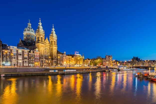 Orizzonte della città di amsterdam con la costruzione del punto di riferimento alla notte nei paesi bassi