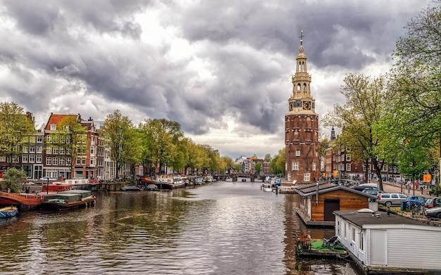 Paesaggio urbano di amsterdam con le tipiche case olandesi medievali dei battelli sul canale e la torre di montelbaanstoren