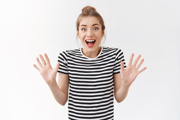 Divertito, allegro seducente giovane donna creativa con panino disordinato in t-shirt a righe ha ottime notizie, vuole sorprendere gli amici con un suggerimento fantastico, alzare le mani gesticolando e sorridere ampiamente