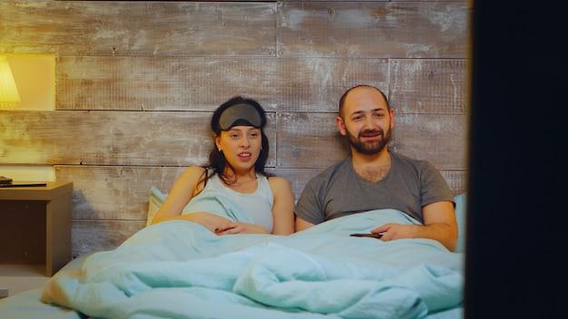 Coppia divertita che indossa un pigiama sdraiato a letto guardando uno spettacolo televisivo. am facut doar parole chiave; mai tre titlurile
