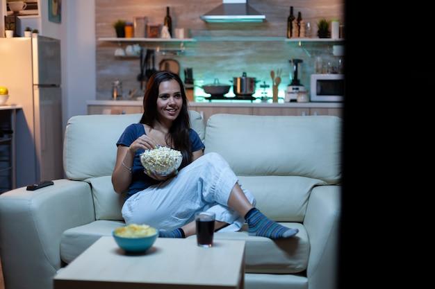 Signora divertita che guarda un programma televisivo di notte seduta sul divano
