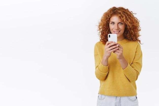 Donna riccia rossa divertita in maglione giallo, tenendo in mano lo smartphone e sorridendo compiaciuta, registra video, scatta foto, spara a un amico per i social network o partecipa a un concerto fantastico, muro bianco