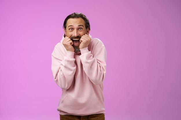 Divertito entusiasta ansimante bell'uomo adulto barbuto felice in felpa con cappuccio rosa chinandosi urlando con gioia riceve incredibile incredibile presente in piedi senza parole eccitato sfondo viola. copia spazio