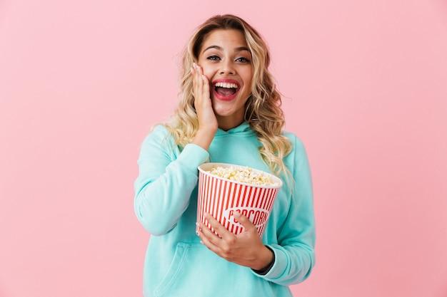 Donna divertente che tiene la benna con popcorn e che guarda l'obbiettivo, isolata sopra la parete rosa