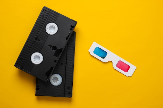 Occhiali 3d di carta usa e getta anaglifi e videocassetta su sfondo giallo. media retrò, intrattenimento anni '80. vista dall'alto