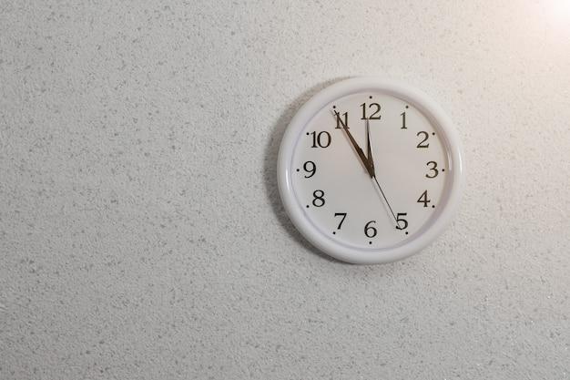 Orologio analogico con lancette sul muro con intonaco strutturato. dispositivo per la determinazione dell'ora.