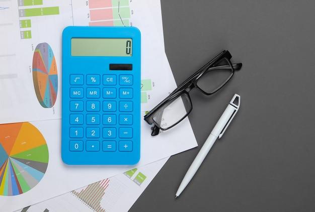 Analisi delle statistiche. calcolo economico. calcolatrice, bicchieri, grafici e tabelle su grigio. lay piatto