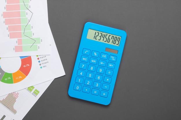 Analisi delle statistiche. calcolo economico. calcolatrice, grafici e tabelle su grigio. lay piatto