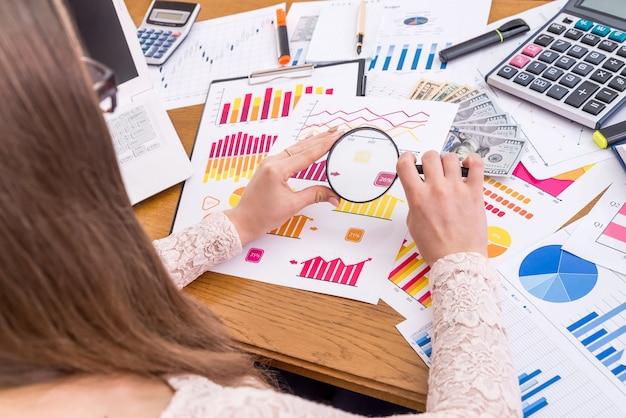 Analista che ingrandisce i grafici aziendali in ufficio, sul posto di lavoro