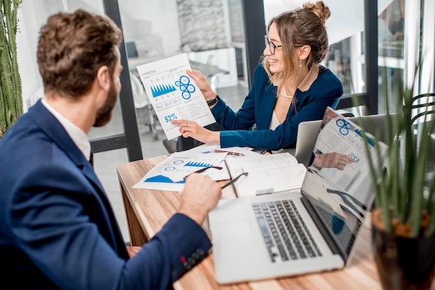 Team di manager analitici che lavora con grafici cartacei e laptop in ufficio