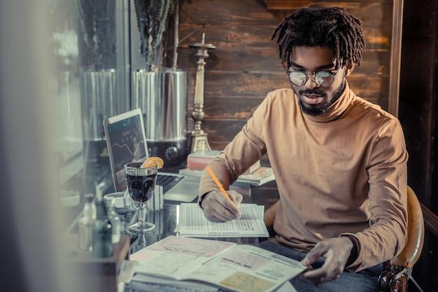 Fai analisi. soddisfatto uomo barbuto chinando la testa durante il controllo dei documenti